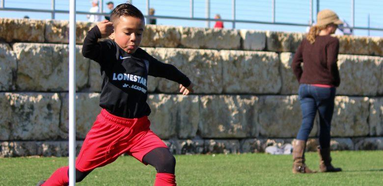 boy kicking a soccer ball - how to make sports fun for kids