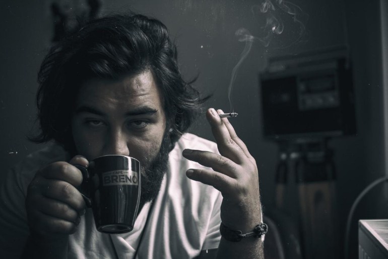 a man drinking coffee and smoking a cigarette